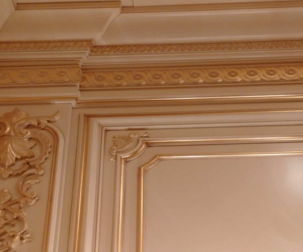 Cornice and architrave enriched with wooden moldings carved and finished with gold leaf